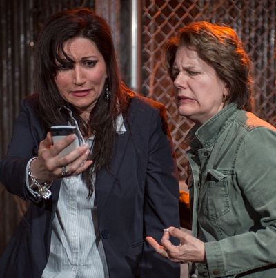 Sam (Mierka Girten, left) shares a disturbing photo from home with Beth (Natalie West) in 'Mud Blue Sky.' (Michael Brosilow)