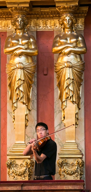 CSO Viola Danny Lai warms up among the golden caryatids adorning the interior of the Musikverein. (Todd Rosenberg)