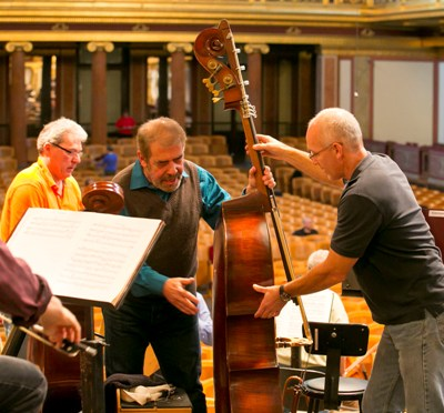 Todd Snick assists CSO Joe DiBello with his double bass at the Musikverein. It will be a tight squeeze. (Todd Rosenberg)