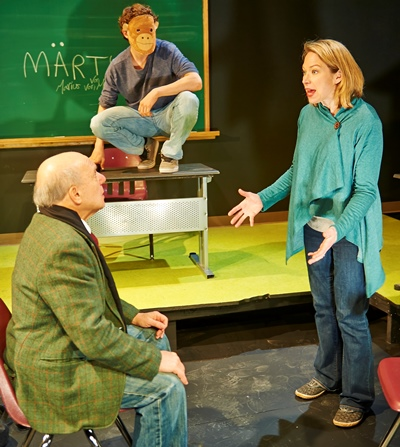 Headmaster Batzler (Walter Brody) listens to science teacher Erika Roth (Kendra Thulin) justify evolution as masked, mocking student Benjamin (Brando Crawford) looks on. (Lee Miller)