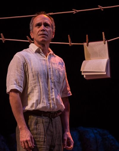 A girl's world-weary father (Henry Godinez) subjects a book to a test of the elements. (Liz Lauren)