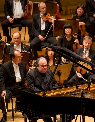 Chen, in his work-a-day world, behind pianist Yefim Bronfman, awaiting his next cue. (Todd Rosenberg)