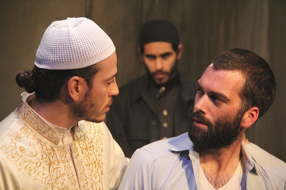 Nick (Joel Reitsma) negotiates his ransom with the imam (Bassam Abdelfattah) as Bashir (Owais Ahmed) looks on.