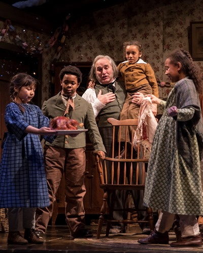 Bob Cratchit (Ron E. Rains) hoists Tiny Tim (Paris Strickland) on his shoulders as the family eyes their Christmas goose. (Liz Lauren)